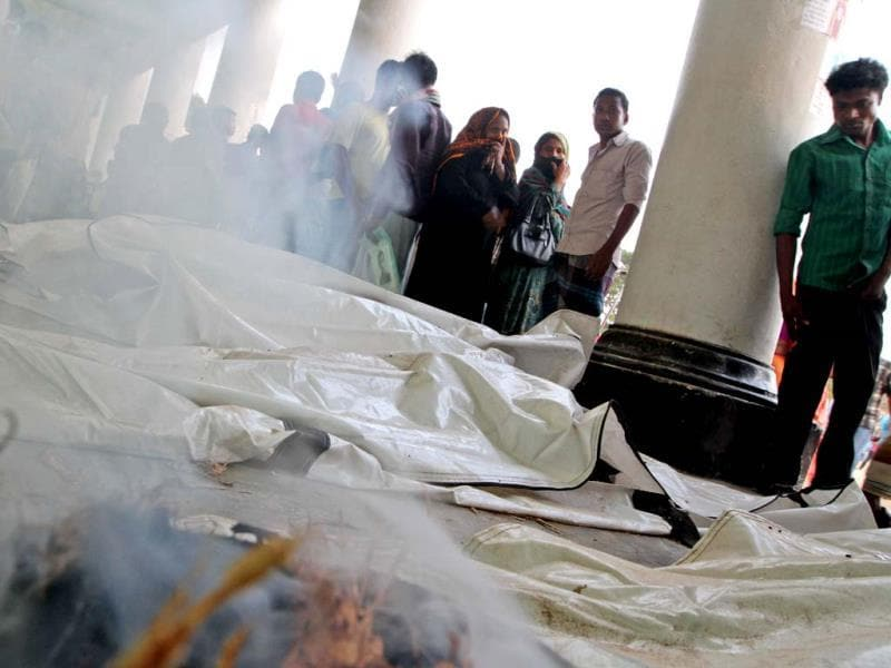 Smoke rises from incense lit to mask the smell of rotting bodies, as kin stand to identify victims of a building that collapsed, in Savar, near Dhaka. AP photo