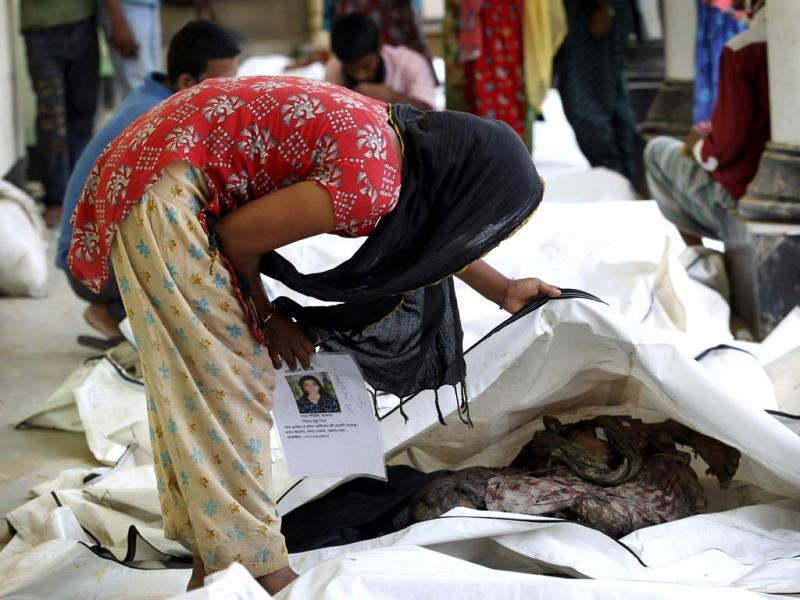 A woman looks through a line of bodies that were retrieved from a collapsed garment factory building in hopes of identifying her relative in Savar, near Dhaka. AP photo