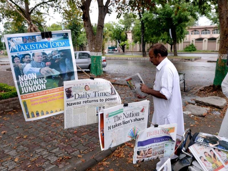 Pakistani men look at morning newspapers with front-page-coverage of Nawaz Sharif's success in the elections the day before, along a roadside stall in Islamabad. AFP Photo