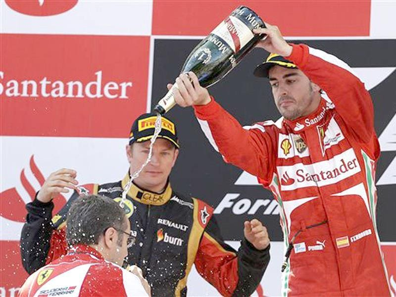 Ferrari driver Fernando Alonso of Spain pours Champagne on team principal Stefano Domenicali, as second place Lotus driver Kimi Raikkonen of Finland watches on the podium. AP Photo