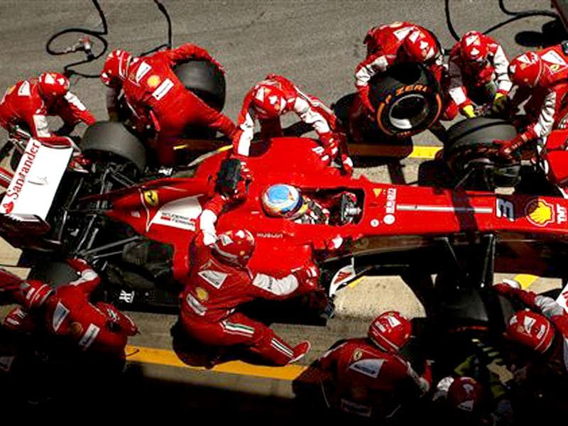 Mechanics of Ferrari driver Fernando Alonso of Spain change the wheels of his car during the Formula One Spanish Grand Prix. AP Photo
