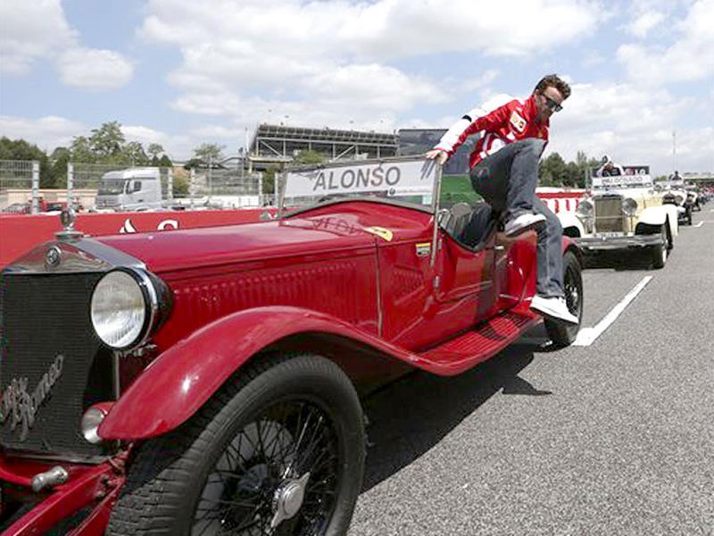 Ferrari driver Fernando Alonso of Spain jumps from a classic car during the driver's parade prior to the start of the Formula One Spanish Grand Prix. AP Photo