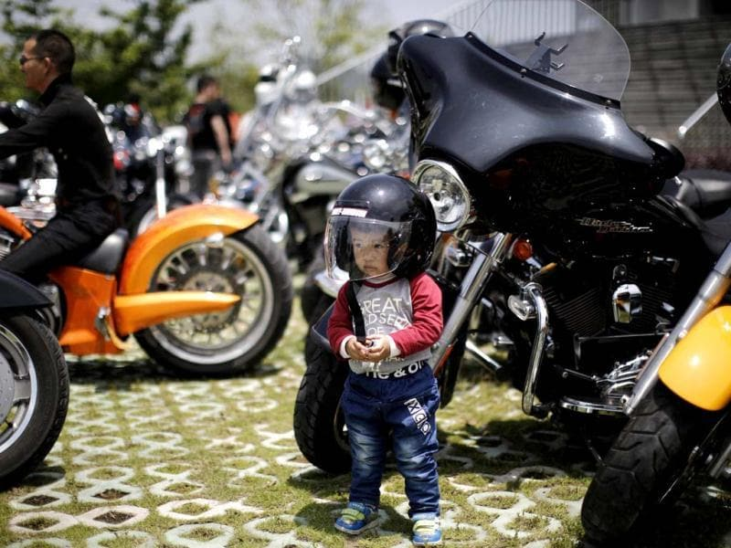 A local boy wearing a helmet poses next to a Harley Davidson motorcycle during the annual Harley Davidson National Rally in Qian Dao Lake, in Zhejiang Province.