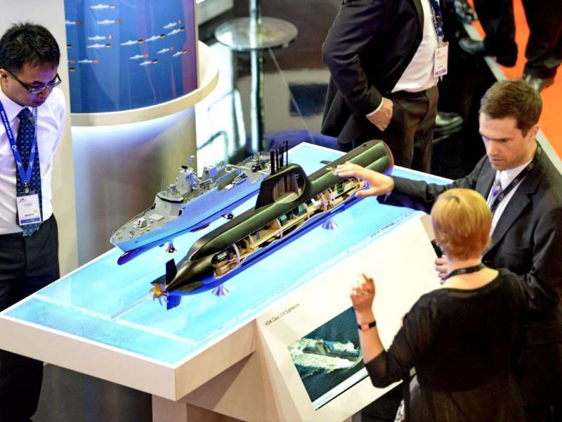 Visitors look at an exhibit of a naval vessel and a submarine displayed at the International Maritime Defence Exhibition (IMDEX) Asia 2013 in Singapore. (AFP)