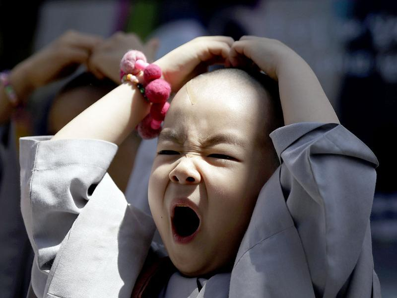 A shaven-headed young boy yawns while attending a volunteer activity in Seoul, South Korea. He is among ten children who entered a temple to have an experience of monks' life for three weeks, called Little Buddha Camp, to celebrate upcoming Buddha's birthday on May 17. AP Photo