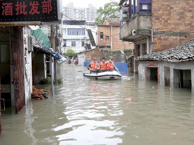 Rescuers paddle a boat to transport residents on a flooded street after a heavy rainstorm hit Nanchang, Jiangxi province. Reuters