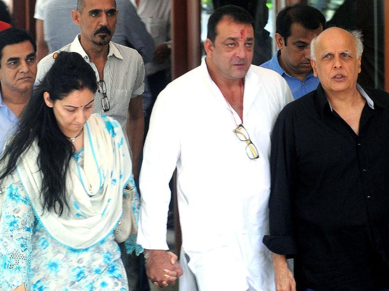 Actor Sanjay Dutt accompanied by his wife Manyata, film director Mahesh Bhatt and other friends leaving his residence to surrender before the TADA court in Mumbai on Thursday. (PTI Photo)