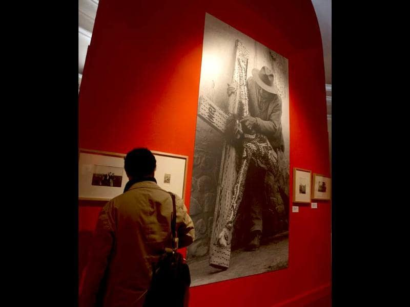 A visitors looks at historical photographs displayed during the unveiling of the exhibition