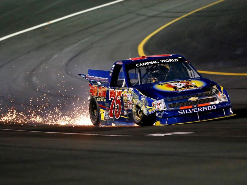 Caleb Holman, driver of the #75 Alpha Dog/Highland Hickory Market Chevrolet, trails sparks after an incident during the NASCAR Camping World Truck Series North Carolina Education Lottery 200 at Charlotte Motor Speedway in Concord, North Carolina. (AFP Photo)
