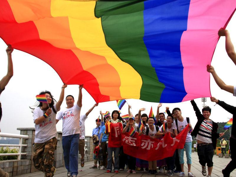 Activists raise a rainbow flag as they march during a demonstration to mark the International Day Against Homophobia and Transphobia in Changsha, Hunan province. (Reuters)