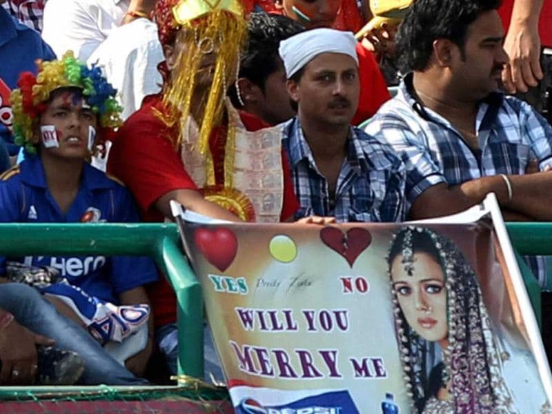 A cricket fan, dressed up as groom, holds a poster of actress and co-owner of Kings XI Punjab Preity Zinta that reads 'Will You Marry Me' during the team's T20 match against Mumbai Indians in Dharamshala. (PTI)