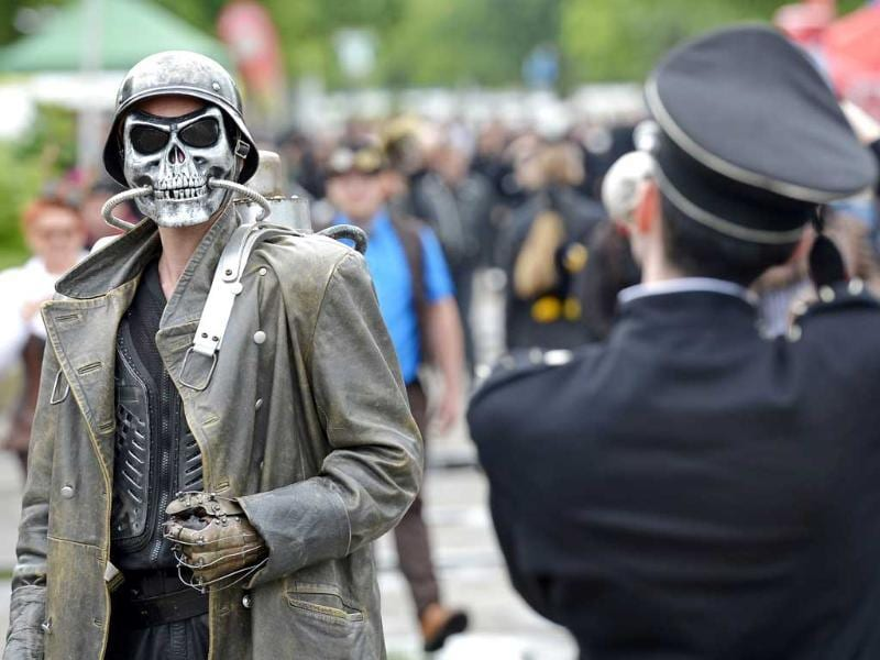 A participant of the gothic music festival Wave Gothic Festival is pictured by another one as he walks in Leipzig, central Germany. AP