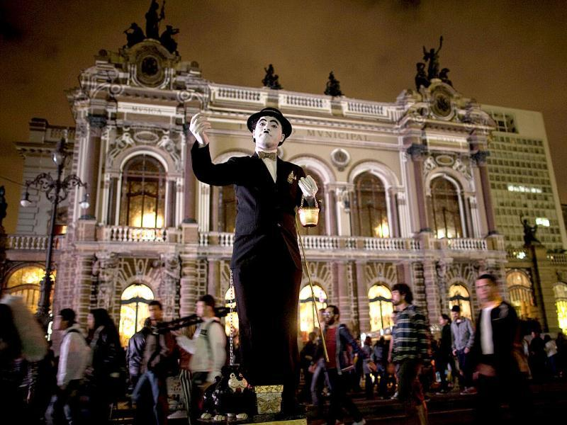 An artist dressed as Charlie Chaplin performs in front of Municipal Theater as part of the annual art event Virada Cultural in Sao Paulo, Brazil. (AP Photo)