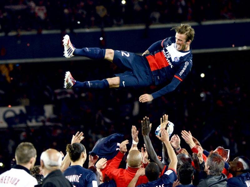 Paris Saint-Germain's English midfielder David Beckham is thrown in the air by teammates after a French L1 football match between Paris St Germain and Brest at Parc des Princes stadium in Paris. (AFP Photo)