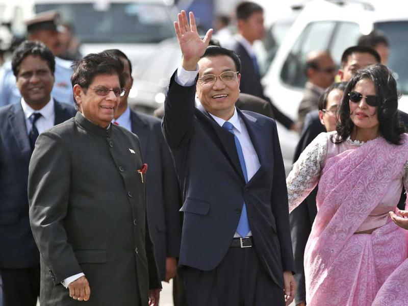 Chinese Premiere Li Keqiang waves as he is received by minister of state for external affairs E Ahamed, left, after he arrives in New Delhi. (AP Photo)