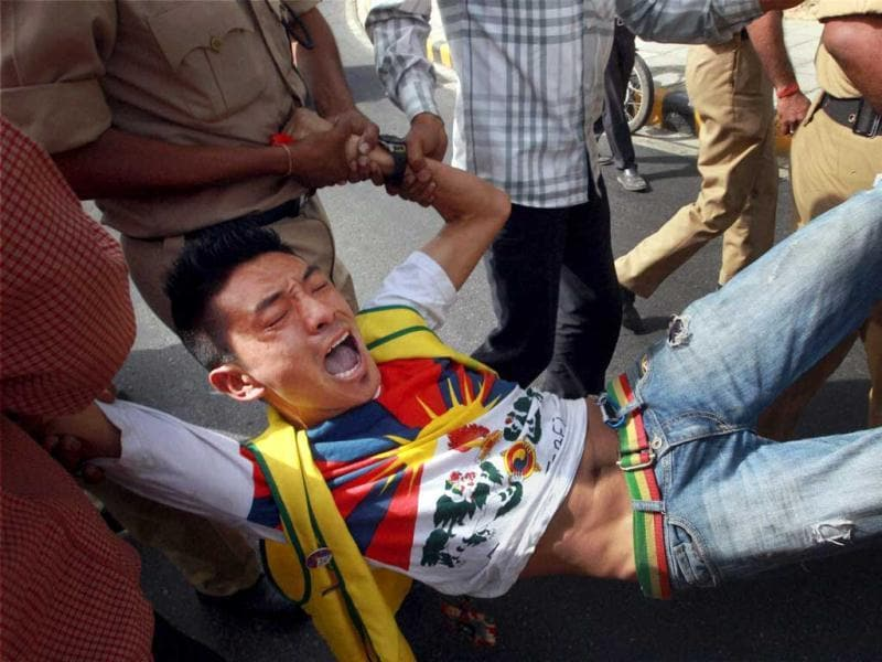 Policemen control Tibetans protesting against the visit of Chinese Premier Li Keqiang outside the Chinese embassy in New Delhi. PTI Photo