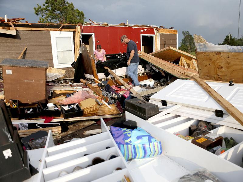 Nancy and Jason Townsend sort through belongings after their home was hit by a tornado in Carney Oklahoma. The Townsend's left their home to avoid the tornado. AP Photo