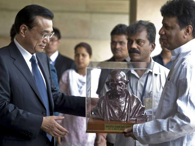 Premier of China Li Keqiang (L) recieves a memento during his visit at Rajghat, memorial for Mahatma Gandhi, in New Delhi. AFP Photo