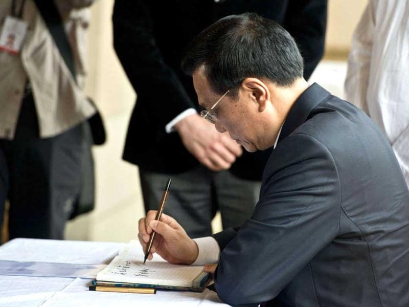Premier Li Keqiang signs the visitors' book during his visit to Rajghat, memorial for Mahatma Gandhi, in New Delhi. AFP Photo