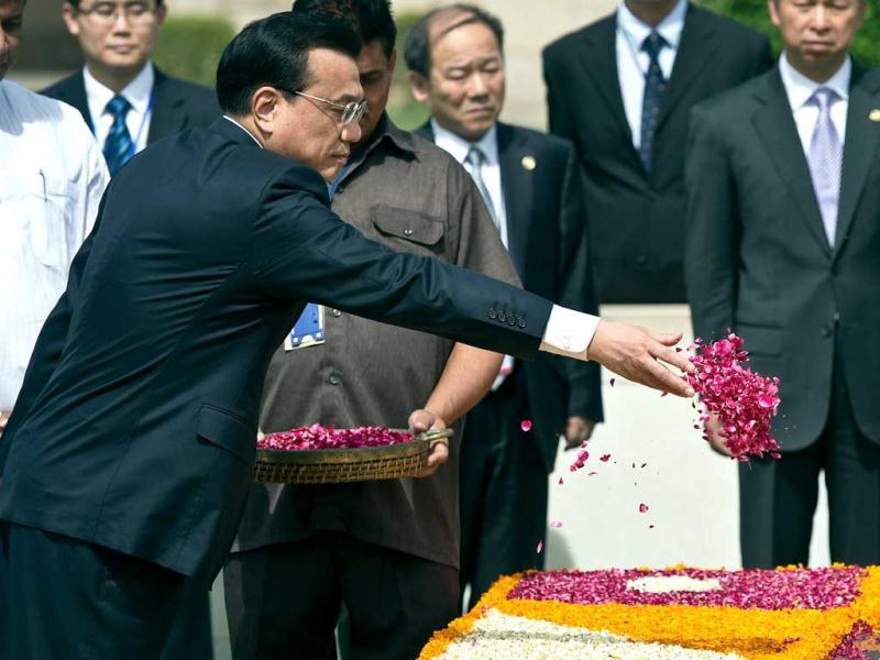 Prime Minister of the People's Republic of China Li Keqiang (L) sprinkles rose petals while paying tribute at Rajghat, memorial for Mahatma Gandhi, in New Delhi.   AFP Photo