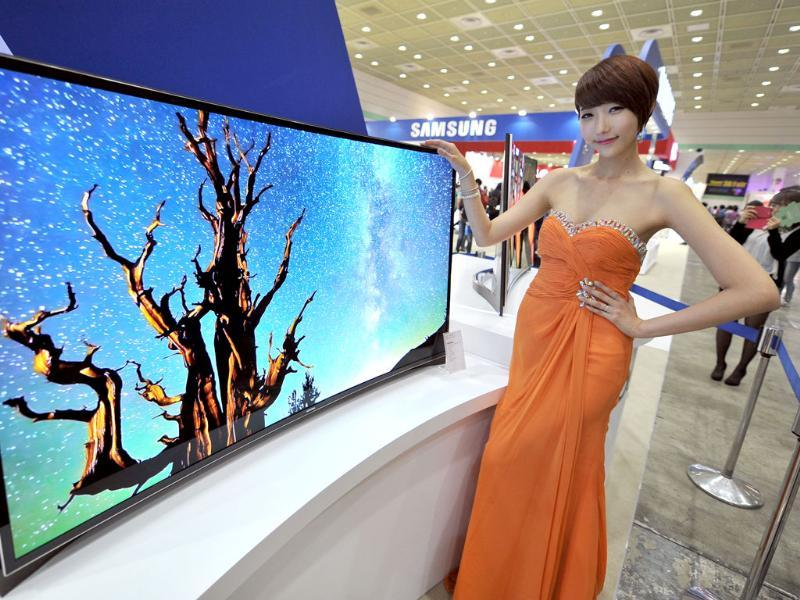 A South Korean model poses with a 55-inch curved OLED TV of Samsung Electronics during an IT show in Seoul. South Korea's largest consumer electronics and technology trade fair kicked off in Seoul, showcasing the latest mobile gadgets and telecommunications technologies. AFP