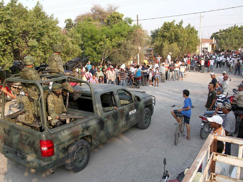 Mexican army soldiers enter the town of La Ruana, Michoacan, Mexico. Residents of western Mexico towns who endured months besieged by a drug cartel are cheering the arrival of hundreds of Mexican army troops. AP