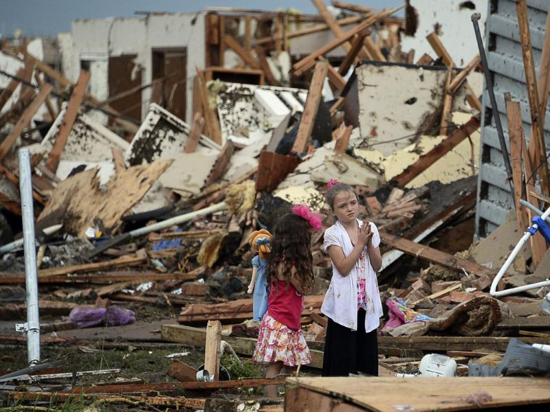 People are seen next to a damaged house and vehicles along a street after a huge tornado, in Moore, Oklahoma. Reuters