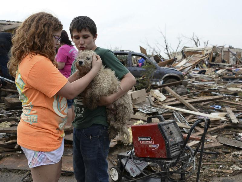 Abby Madi and Peterson Zatterlee comforts Zaterlee's dog Rippy, after a tornado struck Moore, Oklahoma. Reuters