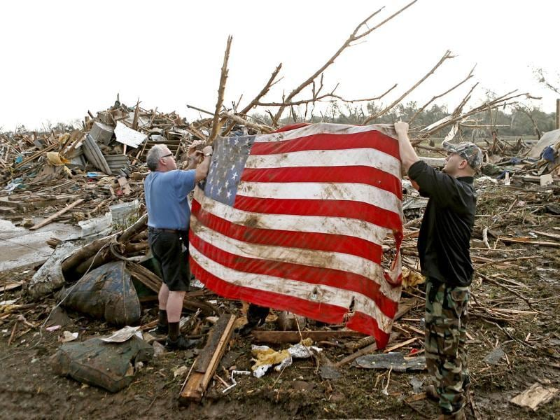 Clark Gardner and another man place an American flag on debris in a neighborhood off of Telephone Road in Moore, Oklahoma, after a tornado moved through the area. AP