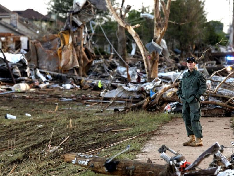 A member of a security team helps guard an area of rubble from a destroyed residential neighborhood, one day after a tornado moved through Moore, Oklahoma. AP photo