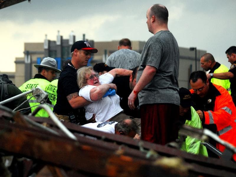 Emergency workers rescue a woman from a building that was destroyed off of 4th Street and Interstate 35 after a tornado ripped through Moore, Oklahoma. AP photo