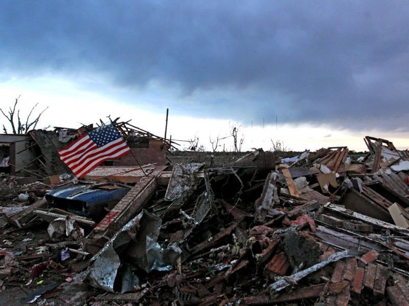 An American flag blows in the wind at sunrise atop the rubble of a destroyed home a day after a tornado moved through Moore, Oklahoma. AP photo