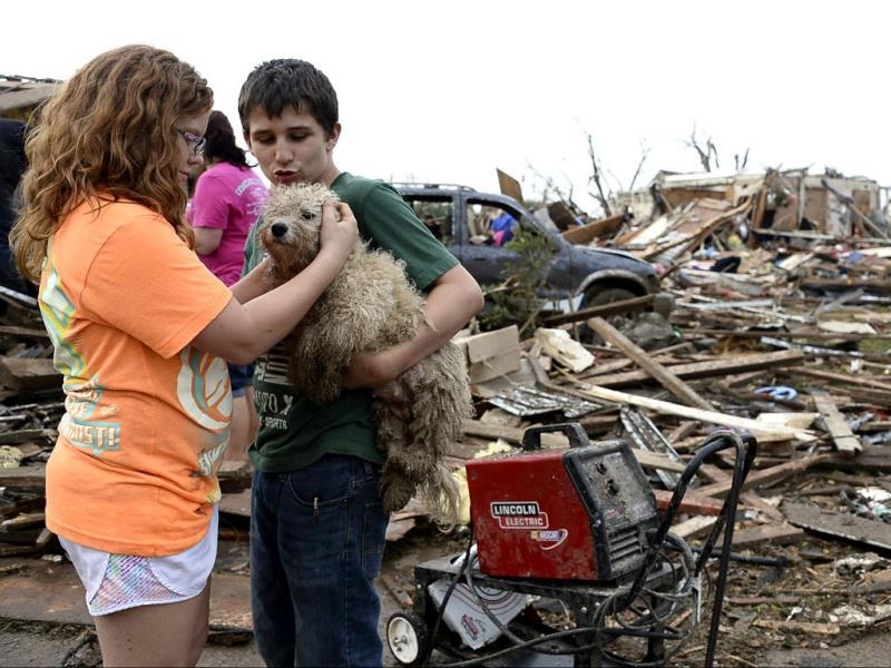 Abby Madi (L) and Peterson Zatterlee comforts Zaterlee's dog Rippy, after a tornado struck Moore, Oklahoma. Reuters photo