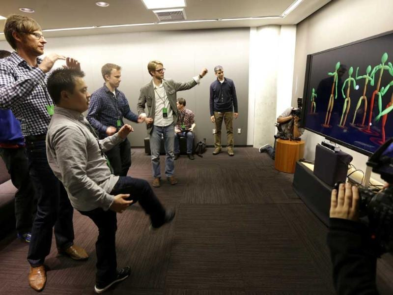 A group of visiting journalists try out the improved motion-detecting capabilities of the new Kinect controller for Microsoft's next-generation Xbox One entertainment and gaming console system. Photo: AP/Ted S. Warren