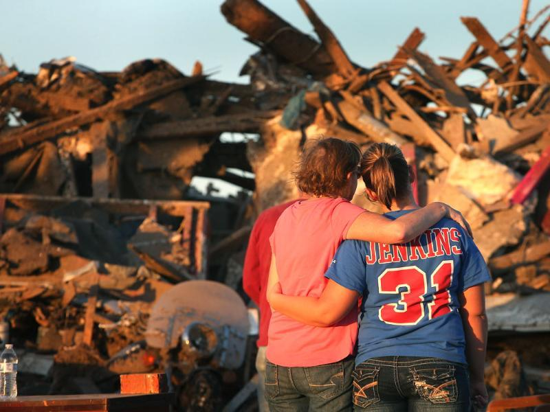 Christine Jones is comforted by her daughter Ashley as they stand in front of Christine's home which was destroyed when a tornado ripped through the area in Moore, Oklahoma. AFP/Getty Images