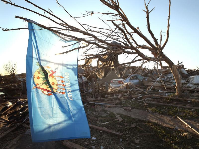 An Oklahoma state flag hangs in a tree next to a destroyed home across the street from the Plaza Towers Elementary School where several children died during a tornado that ripped through the area in Moore, Oklahoma. AFP/Getty Images
