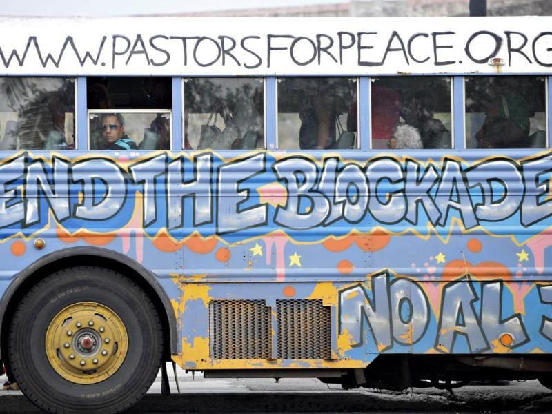 A man sits in a bus donated by the Pastors of Peace adorned with graffiti demanding an end to the US trade embargo on Cuba in Havana. Pastors for Peace is a US-based group opposed to the 50-year long-standing US economic embargo against communist-ruled Cuba. Reuters