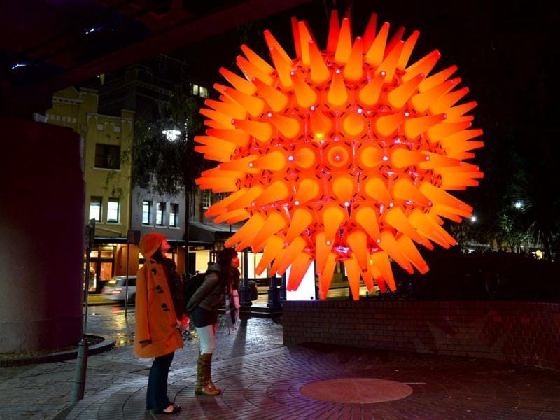 People inspect a light installation as landmarks around the city become part of Sydney's annual festival of light, music and ideas. (AFP)