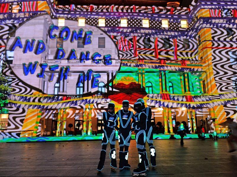 Rollerbladers pose in front of Customs House which is lit up by a projection in Sydney's annual festival of light, music and ideas. (AFP)