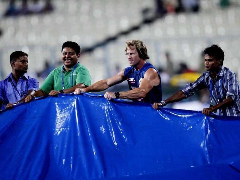 Jonty Rhodes, Mumbai Indians fielding coach helps ground staff to wiped the water from the ground as rain delay the semifinal match between the Mumbai Indians and Rajasthan Royals at Eden Gardens in Kolkata. HT photo/Ajay Aggarwal