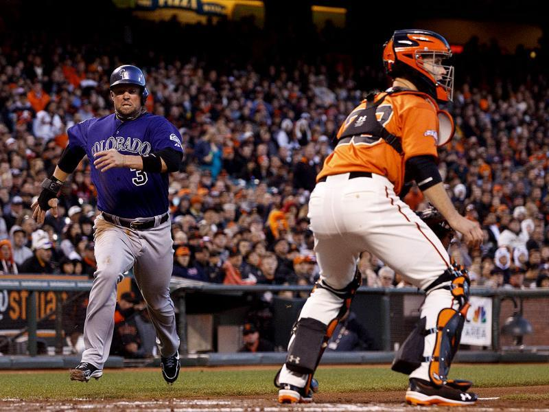 Michael Cuddyer of the Colorado Rockies scores a run past Buster Posey of the San Francisco Giants during the fourth inning at AT&T Park in San Francisco, California. AFP/Getty Images