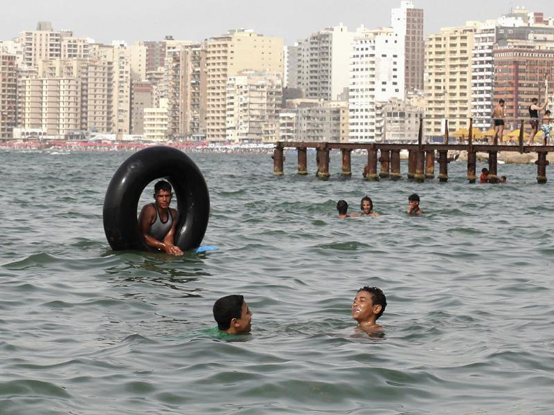Youths swim at the sea to cool off on a hot day in the Mediterranean city of Alexandria. Reuters