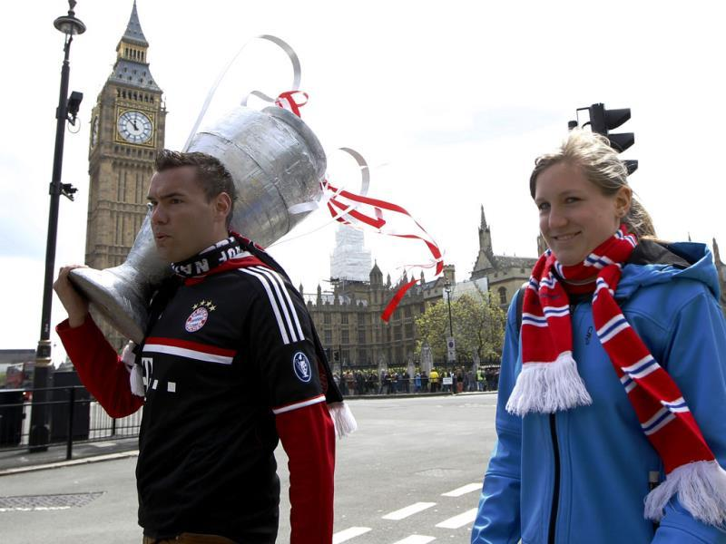 A Bayern Munich supporter carries a replica trophy near the Houses of Parliament as soccer supporters of Boussia Dortmund and Bayern Munich gather in central London ahead of their Champions League final soccer match at Wembley Stadium. AP Photo
