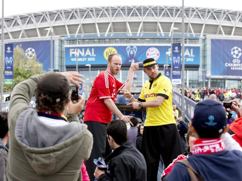 Fans take pictures of men in stilts as they arrive at Wembley Stadium in London ahead the UEFA Champions League football final between Bayern Munich and Borussia Dortmund at Wembley Stadium. AFP Photo