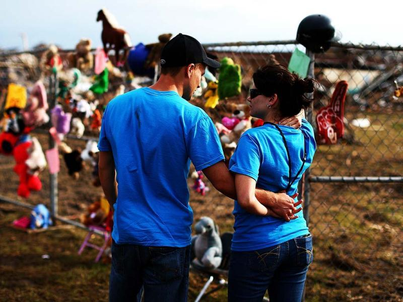 (L-R) CJ Bellavia and Olivia Bellavia embrace while visiting a makeshift memorial outside the tornado ravaged Plaza Towers Elementary School in Moore, Oklahoma. The tornado of EF5 strength and two miles wide touched down on May 20 killing at least 24 people and leaving behind extensive damage to homes and businesses. U.S. President Barack Obama promised federal aid to supplement state and local recovery efforts. (AFP)