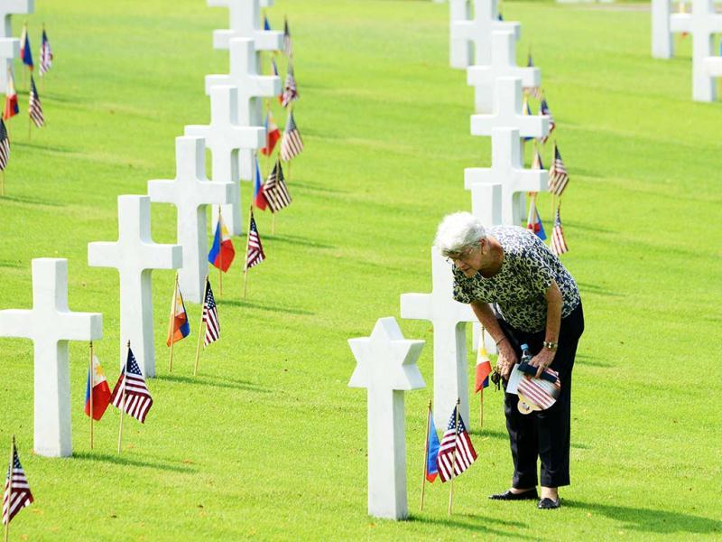 A woman looks at the grave of a soldier who fell during World War II, during services to mark US Memorial Day at the Manila American Cemetery in Fort Bonifacio in Manila. At least 17,000 graves are in the park that pays tribute to US and Philippines soldiers that fought side-by-side during World War II. The US marks Memorial Day on May 27. (AFP)