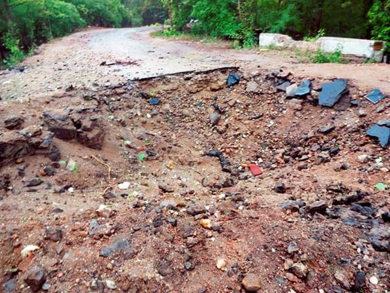 A crater is seen on the road on in Bastar where Maoists attacked Congress party's convoy. PTI Photo