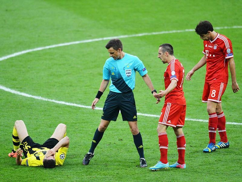 Borussia Dortmund's Polish striker Robert Lewandowski lies on the floor as the Italian referee Nicola Rizzoli looks on and Bayern Munich's French midfielder Franck Ribery reacts during the UEFA Champions League final football match between Borussia Dortmund and Bayern Munich at Wembley Stadium in London. AFP