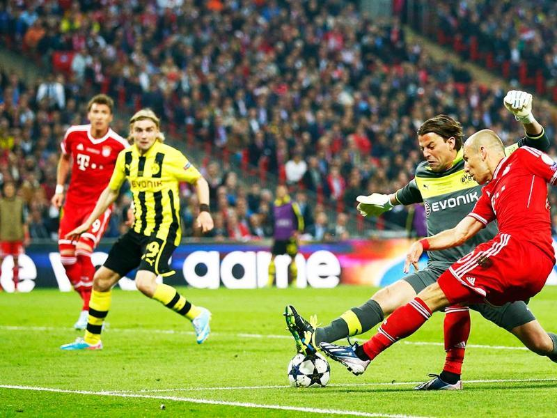 Bayern Munich's Arjen Robben passes the ball past Borussia Dortmund's goalkeeper Roman Weidenfeller to team mate Mario Mandzukic to score during their Champions League Final soccer match at Wembley Stadium in London. Reuters