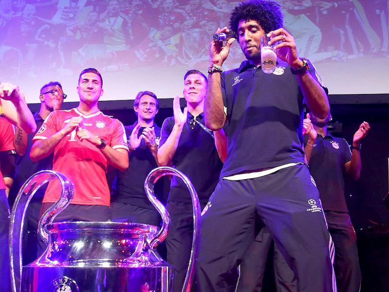 Bayern Munich's Brazilian defender Dante dances beside the trophy as he takes part in the celebration banquet in London. (AFP)